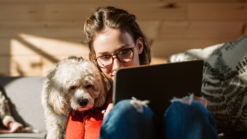 girl browsing tablet with her dog